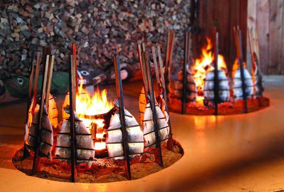 Fish roasting at Tillicum Village. Photo by WA Tourism Association.